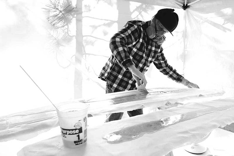 Corey Smith spreads an even layer of fiberglass on some snowboards.